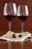 Two glasses of wine on a wooden table. Candies. Stock Photos