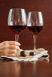 Two glasses of wine on a wooden table. Candies. Hands. Royalty Free Stock Photography