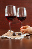 Two glasses of wine on a wooden table. Candies. Hands. Stock Image