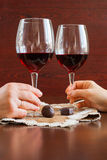 Two glasses of wine on a wooden table. Candies. Hands. Royalty Free Stock Images