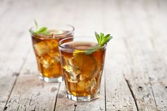 Two Glasses With Traditional Iced Tea With Lemon, Mint Leaves And Ice Cubes In Glass On Rustic Wooden Table Background Stock Photography