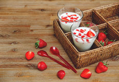 Two Glasses of Yogurt,Red Fresh Strawberries in the Rattan Box with Plastic Spoons on the Wooden Table.Breakfast Organic Healthy T Royalty Free Stock Photo