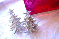 Two glittery Christmas trees in front of glittery bright pink gi royalty free stock image