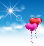 Two glossy hearts balloons for Valentine Day flying in the blue Stock Images