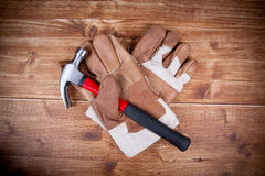 Two Glove and Stell Hammer. On Vintage wood backgpund Stock Images