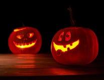 Two glowing jack o lantern pumpkins Royalty Free Stock Images