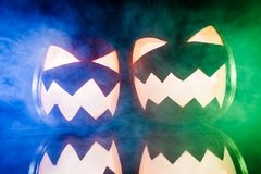 Two glowing pumpkins for Halloween with color lights. On black background Royalty Free Stock Photography