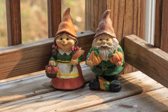 Two gnomes with holding pumpkins. Two gnomes with pumpkins and wheat crops harvesting Royalty Free Stock Image