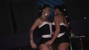 Two go go girls in black bikini sexy dance together on stand in nightclub. stock video footage