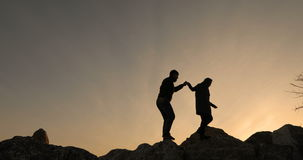 Two go on rocks, against a sunset. stock footage