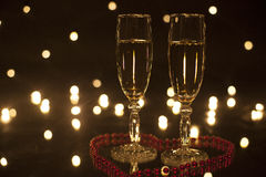 Two goblet of white wine in heart lined with beads. Twinkle lights on background. Filled wine glasses while standing in the heart laid out beads. Isolated on royalty free stock photos