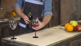 Two goblet on the wooden desk with drink. Guy pouring wine into wineglass close-up details in the kitchen. Man hands holding bottle. On the cook table different stock video