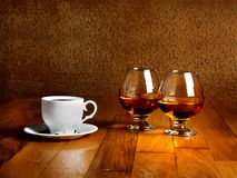 Two goblets of brandy and cup of hot coffee Stock Photo