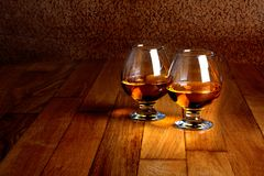 Two goblets of brandy on wooden counter top Royalty Free Stock Image