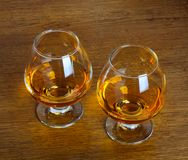 Two goblets of brandy on wooden counter top Royalty Free Stock Photo