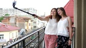Two gogeous women on the balcony taking a selfie. Slow motion stock footage