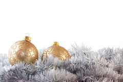 Two gold baubles in silver garland Royalty Free Stock Photography