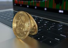 Two Gold Bitcoin virtual money on laptop keyboard, close-up stock images