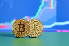 Two gold bitcoins lie on the green surface on the background of. The display, which depicts the growth of the position on the chart Royalty Free Stock Photos