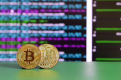 Two gold bitcoins lie on the green surface on the background of Stock Photo