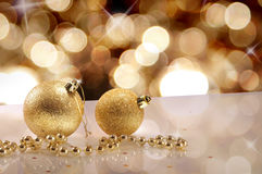 Two gold Christmas balls and pearls with golden bokeh. Christmas concept with two gold Christmas balls and pearls on a white table methacrylate close up. Golden Royalty Free Stock Photos