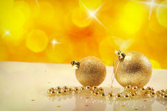 Two gold Christmas balls and pearls with yellow bokeh. Christmas concept with two gold Christmas balls and pearls on a white table methacrylate close up. Yellow Royalty Free Stock Photo
