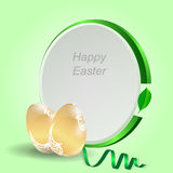 Two gold Easter eggs with a green tag on a light green background with ribbon. Stock Images