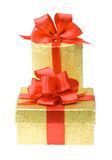Two gold gift boxes with red ribbons. Isolated Royalty Free Stock Photography