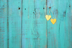 Two gold hearts hanging on antique teal blue wood fence