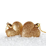 Two gold hearts on snow Stock Photo