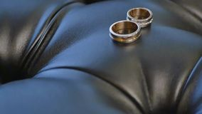 Two gold rings on the leather sofa stock video