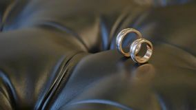 Two gold rings on the leather sofa stock footage