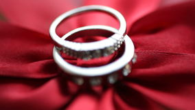Two gold rings on a red bow stock footage