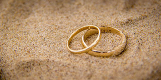 Two gold rings on sand. Macro close up of two simple gold rings sitting on sand Royalty Free Stock Photography