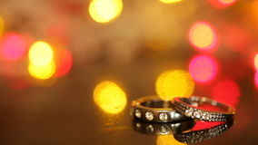 Two gold rings on the table and a colorful bokeh. Of garlands on the background stock video