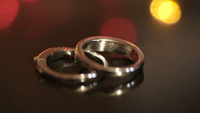 Two gold rings on the table and a colorful bokeh. Of garlands on the background stock video footage