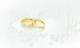 Two Gold Rings for a Wedding Day. Two Gold Wedding Rings with Heart of pearls Stock Photos