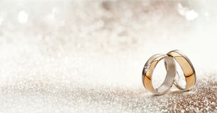Two gold wedding bands on textured glitter