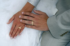 Two gold wedding rings on brides's wedding dress. Couple's hands with two gold wedding rings on bride's wedding dress Stock Photo