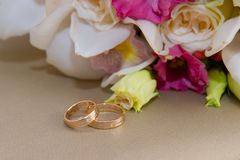 Two gold wedding rings with diamond lie around the bride's bouquet of white orchids and pink flowers. Stock Image
