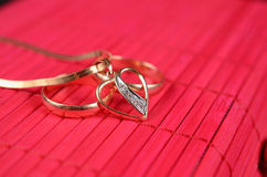 Two gold wedding rings and gold heart. With chain on the red bamboo surface royalty free stock photos