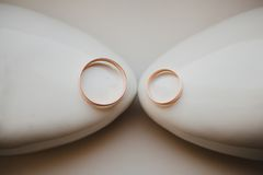 Two gold wedding rings laying on white bridal Stock Photos