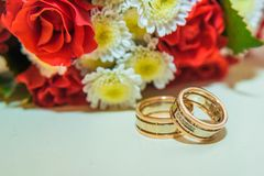 Two gold wedding rings lie and a bouquet of red roses. Royalty Free Stock Photography