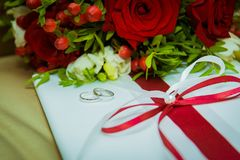 Two gold wedding rings lie and a bouquet of red roses. Stock Photos