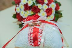 Two gold wedding rings lie and a bouquet of red roses. Royalty Free Stock Image