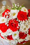 Two gold wedding rings lie on a bouquet of red and white roses. Royalty Free Stock Photo