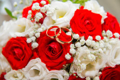 Two gold wedding rings lie on a bouquet of red and white roses. Royalty Free Stock Photography