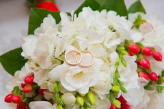 Two gold wedding rings lie on a bouquet with white flowers and red berries. Stock Photo