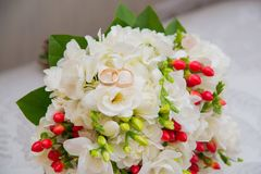 Two gold wedding rings lie on a bouquet with white flowers and red berries. Stock Image