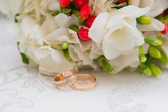 Two gold wedding rings lie on a bouquet with white flowers and red berries. Stock Photos